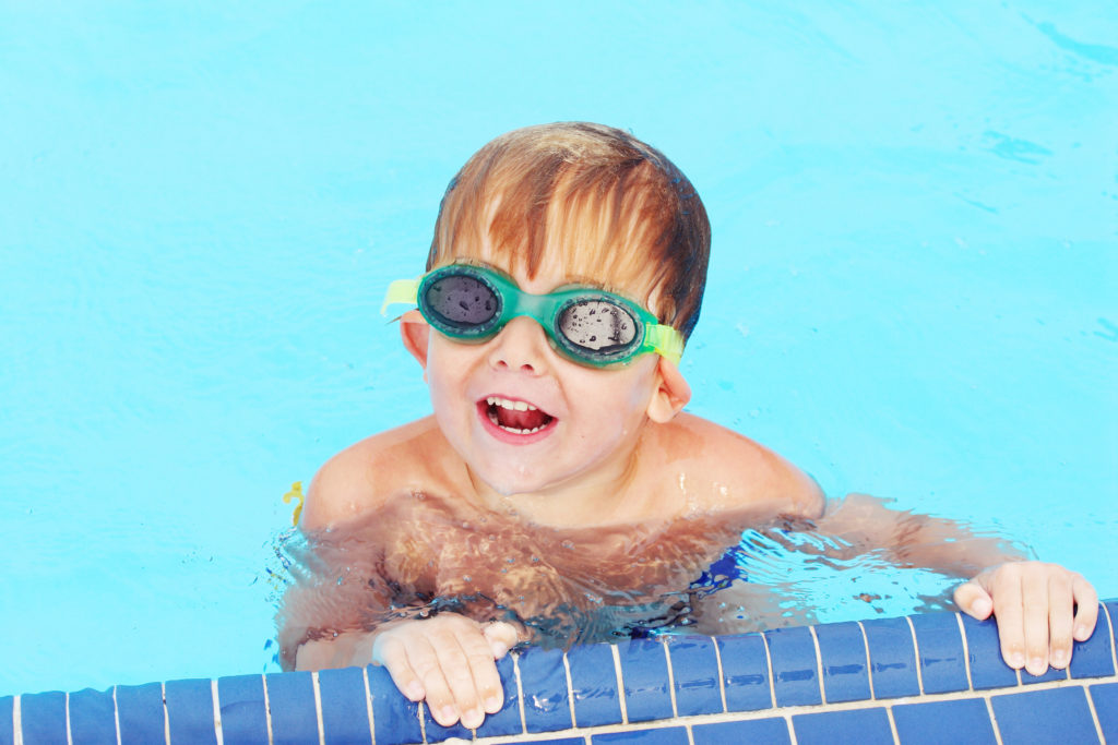 Smiling boy swimming in pool